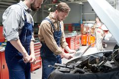 Dos mecánicos que examinan el coche imágenes de archivo libres de regalías