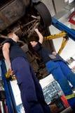 Dos mecánicos que miran el coche Imagenes de archivo