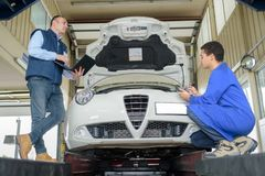Dos mecánicos que trabajan en el coche Foto de archivo libre de regalías