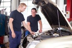 Dos mecánicos que trabajan en un coche Imágenes de archivo libres de regalías