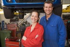 Dos mecánicos que se colocan en la sonrisa del garage Imagenes de archivo