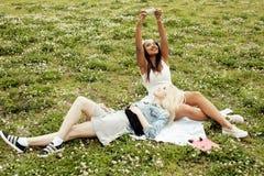 Dos mejores amigos bonitos jovenes de las muchachas del adolescente que ponen en la hierba que hace la foto del selfie que se div Imagen de archivo libre de regalías