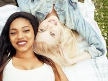 Dos mejores amigos bonitos jovenes de las muchachas del adolescente que ponen en la hierba que hace la foto del selfie que se div Imagen de archivo