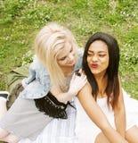 Dos mejores amigos bonitos jovenes de las muchachas del adolescente que ponen en la hierba que hace la foto del selfie que se div Fotografía de archivo libre de regalías