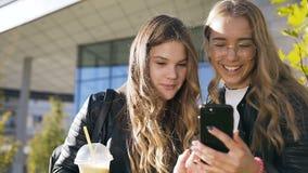Dos mejores amigos caucásicos atractivos alegres de las muchachas que caminan en parque cerca del edificio moderno que ríe mucho  almacen de metraje de vídeo