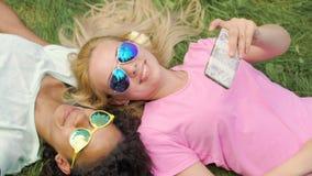 Dos mejores amigos de las muchachas que mienten en el césped, tomando las fotos en el teléfono móvil, diversión en parque almacen de metraje de vídeo