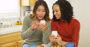 Dos mejores amigos de las mujeres que usan los teléfonos elegantes y comiendo el desayuno fotos de archivo