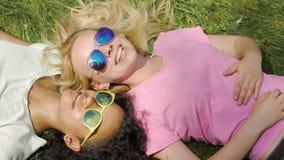 Dos mejores amigos felices de las muchachas que cuelgan hacia fuera en hierba en el parque, disfrutando de fin de semana almacen de metraje de vídeo