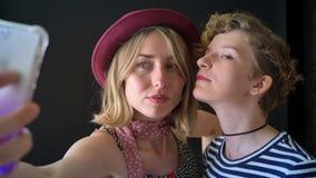 Dos mejores amigos femeninos jovenes que toman el selfie y que sonríen, aislado en fondo negro almacen de metraje de vídeo