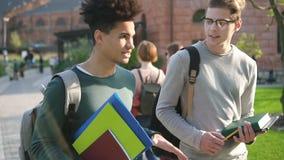 Dos mejores amigos masculinos son que caminan y que hablan cerca de campus metrajes