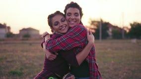 Dos mejores amigos que se abrazan y que miran en la sonrisa de la cámara Abrazo feliz y abrazo de la mujer joven que muestran amo metrajes
