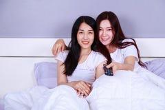 Dos mejores amigos que ven la TV con el telecontrol en cama en dormitorio Fotos de archivo