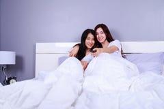 Dos mejores amigos que ven la TV con el telecontrol en cama en dormitorio Foto de archivo