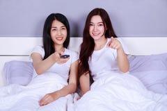 Dos mejores amigos que ven la TV con el telecontrol en cama en dormitorio Fotos de archivo libres de regalías