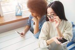 Dos mejores amigos se están sentando en la tabla La muchacha afroamericana está leyendo en el teléfono mientras que su amigo se e Imagen de archivo libre de regalías