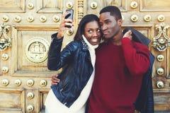 Dos mejores amigos sonrientes que hacen el autorretrato en cámara elegante del teléfono mientras que se oponen a puerta retra, foto de archivo