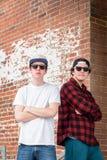 Dos millennials jovenes que presentan por la pared de ladrillo en ciudad Foto de archivo