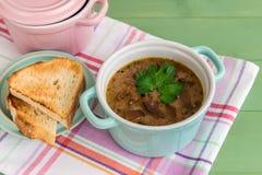 Dos mini cazuelas de sopa de champiñones con la tostada asada a la parrilla imagenes de archivo