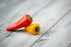 Dos mini pimientas dulces rojas y amarillas en un fondo de madera Fotos de archivo