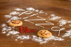 Dos mini pizzas con la salchicha y el queso en la tabla de madera Imágenes de archivo libres de regalías