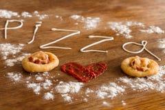 Dos mini pizzas con la salchicha y el queso en la tabla de madera Imagenes de archivo
