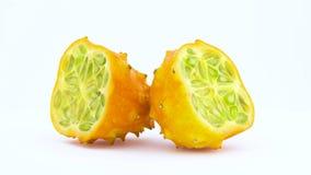 Dos mitades de la fruta madura del kiwano Pulpa verde del kiwano con las semillas Rotación en la placa giratoria aislada en el bl metrajes