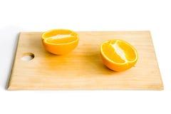 Dos mitades de la naranja en la placa de madera Fotos de archivo libres de regalías