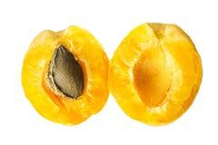 Dos mitades de un albaricoque maduro jugoso de la piña con un hueso dentro Fruta partida en dos aislada en un fondo blanco Visión foto de archivo libre de regalías