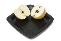 Dos mitades de una manzana en una placa imagen de archivo libre de regalías