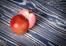 Dos mitades de una manzana roja están en una superficie de madera imágenes de archivo libres de regalías