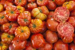 Dos mitades del tomate maduro jugoso en la sección Tomates frescos Tomates rojos Tomates orgánicos del mercado del pueblo Backgro Foto de archivo libre de regalías