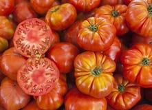 Dos mitades del tomate maduro jugoso en la sección Tomates frescos Tomates rojos Tomates orgánicos del mercado del pueblo Backgro Foto de archivo