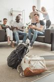 dos mochilas y longboard en primero plano y el grupo de amigos multiétnicos con jugar de las palancas de mando fotos de archivo