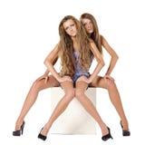 Dos modelos de manera que se sientan en el cubo blanco Imagen de archivo libre de regalías