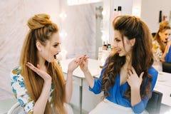 Dos modelos de moda con los makeups elegantes, tocados de lujo que se divierten junto en sal?n del peluquero Amigos junto fotografía de archivo