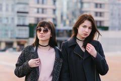 Dos modelos elegantes de las mujeres jovenes se vistieron en actitud casual contra el contexto de la ciudad en un día de primaver Fotografía de archivo libre de regalías