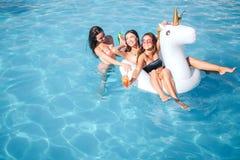 Dos modelos jovenes que nadan en el flotador shaoed unicornio Ellos sonrisas y risa La mujer en frente sostiene el cóctel en mano imagenes de archivo