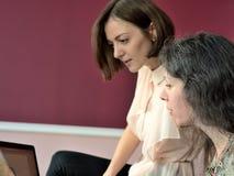Dos modelos ocasional vestidos de las se?oras jovenes se sientan en un escritorio en una oficina del vintage y discuten los docum imagen de archivo
