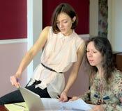 Dos modelos ocasional vestidos de las se?oras jovenes se sientan en un escritorio en una oficina del vintage y discuten los docum fotografía de archivo libre de regalías