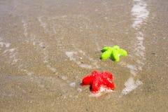 Dos moldes estrella de mar-formados en la arena fotos de archivo