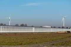 Dos molinoes de viento detrás de un invernadero grande foto de archivo libre de regalías