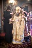 Dos monjes ayudan al obispo al traje Foto de archivo
