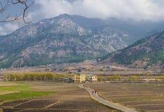 Dos monjes budistas en ropa roja tradicional caminan a lo largo del camino al pueblo Montañas del Himalaya en el horizonte Bhuta imágenes de archivo libres de regalías