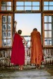 dos monjes en el monasterio miran fuera de ventana el lago Inle Imágenes de archivo libres de regalías