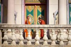 Dos monjes jovenes se encuentran y saludan en pagoda budista Fotografía de archivo