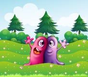 Dos monstruos tuertos adorables cerca de los árboles de pino Fotos de archivo libres de regalías