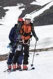 Dos montañeses del esquí suben en la montaña en los esquís atados con correa a las pieles que suben Fotografía de archivo