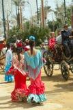 Dos morenitas jovenes en vestidos brillantes del feria miran el paso del caballo y del carro Fotografía de archivo
