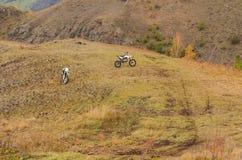 Dos motocicletas a campo través en las montañas en otoño imagenes de archivo