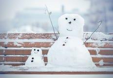 Dos muñeco de nieve, uno grande y uno pequeño Foto de archivo libre de regalías